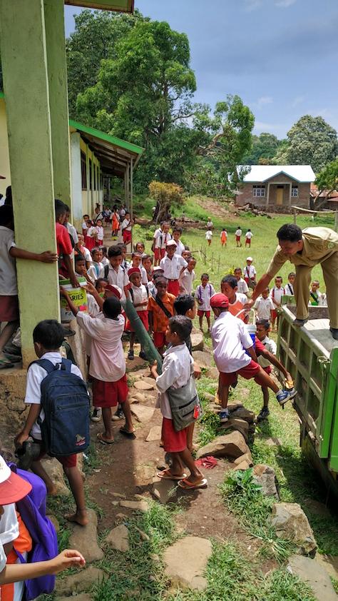 Anak-anak membantu guru menurunkan bahan renovasi perpustakaan